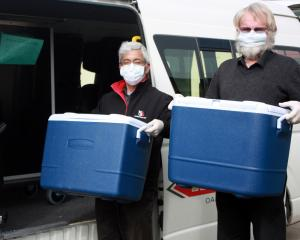 Whitestone Taxis drivers Shige Koyama (left) and Garry Meynell load up with the day's Meals on...