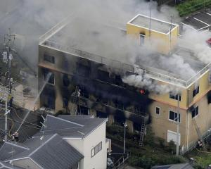 An aerial view shows firefighters battling fires at the site where a man started a fire after...