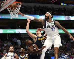 Dallas Mavericks center Willie Cauley-Stein (33) dunks past Denver Nuggets center Nikola Jokic ...