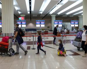 Passengers walk at Dubai International Airport as Emirates airline resumed limited outbound...