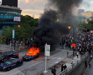 A police car burns near CNN Center in Atlanta, Georgia, as people protest against the death of...