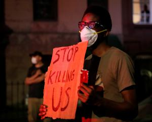 A man wearing a protective face mask holds a sign during a protest in the Brooklyn borough of New...