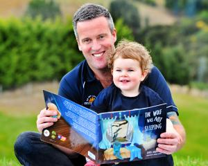 Dunedin firefighter Kris Kennett reads a copy of the book The Wolf Was Not Sleeping to his...