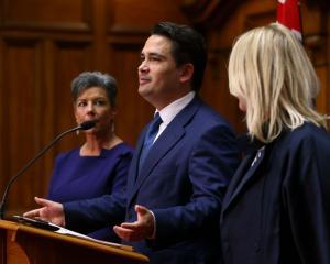 Former National leader Simon Bridges speaks to media while Paula Bennett (L) and wife Natalie...