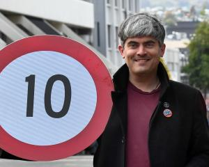 Dunedin Mayor Aaron Hawkins holds a new speed limit sign for George St as he celebrates the...