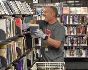 Unlocked, stocked and borrowed ... Dunedin City Library assistant Ian Woodford replenishes the...