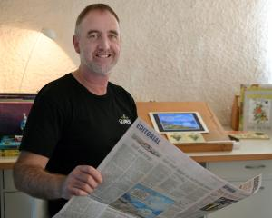 "Otago Daily Times editorial cartoonist Shaun Yeo in his home ""office"", with his trusty desk in..."