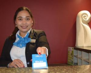 Scenic Hotel Southern Cross senior receptionist Sheena Ragasajo issues a room key in central...