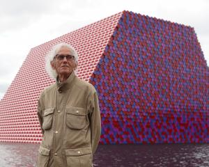 Christo stands in front of his work The London Mastaba, on the Serpentine in Hyde Park in 2018....