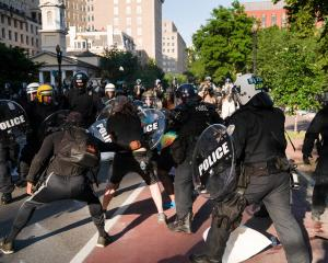 Riot police rush protesters in Lafayette Park in Washington. Photo: Reuters