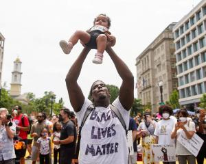 A demonstrator holds up a child during a protest against racial inequality in Washington. Photo:...