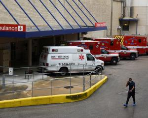 A medical worker walks past a row of ambulances parked outside of Houston Methodist Hospital as...