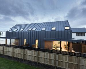 Wide-tray industrial corrugated iron, milled on site, is used for both roof and side facade...