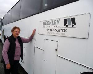 Gay Beckley with one of the buses sitting idle at the moment. Photo: Ashburton Courier