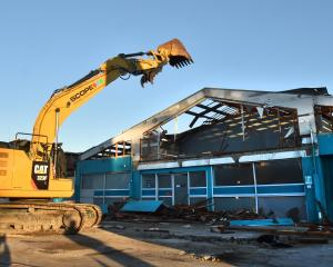 A Scope demolition digger starts to take down the Great King St Caltex site yesterday morning....