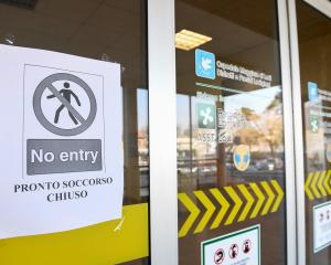 A 'no entry' sign advising that the emergency room is closed is seen on the main entrance of the...