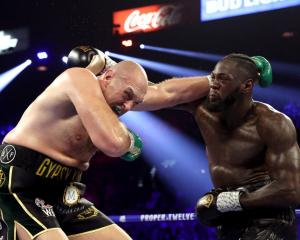 Tyson Fury (L) and Deontay Wilder exchange punches during their heavyweight bout in Las Vegas in...
