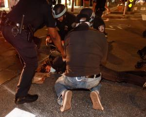 Police officers handcuff a protester after a curfew deadline during a rally in Manhattan...
