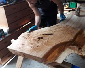 Nick Gyde stains his oak table. Photos: Supplied