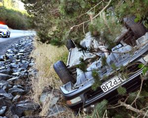 A car rolled on to its roof after coming off the road on State Highway 1, above Evansdale Glen,...