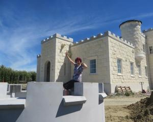 Castle owner Dot Smith examines  one of the castellations to be put atop her creation  today....