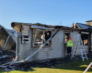 A Fenz firefighter checks on the remains of a house, off Tucker Beach Rd, in Queenstown, which...