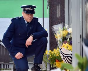 Constable Seaton McGuigan kneels at the entrance to the Dunedin police station to remember...