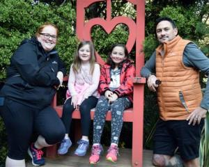 Enjoying a stop at the Queen of Hearts chair in the Larnach Castle garden are (from left) Harriet...