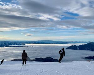 Early snowboarders and skiers take to Treble Cone's Triple Treat slopes on the opening day on...