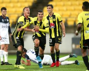 Andrija Kaludjerovic, Goran Paracki and Matthew Ridenton of the Wellington Phoenix celebrate an...