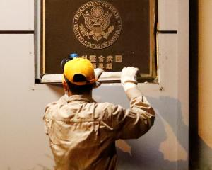 A man removes the plaque at the US Consulate General in Chengdu. China closed the consulate in...
