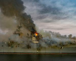 Boats combat a fire on board the US Navy amphibious assault ship USS Bonhomme Richard. Photo: U.S...