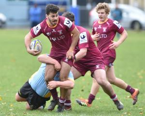 Alhambra-Union second five-eighth Legin Hotham stands in a tackle from University prop Mamea...