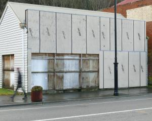 A pedestrian walks past a boarded-up shop in Lawrence's main street on Wednesday; refurbishment...