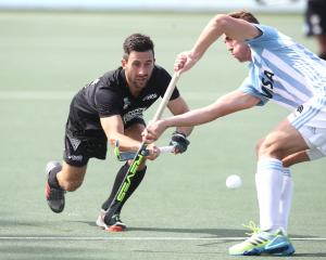 Black Sticks defender Kane Russell competes for the ball with an Argentina player during a men's...