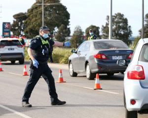 A police officer directs traffic into a checkpoint lane in Melbourne. Photo: Getty