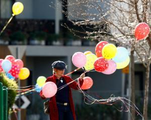 A woman ties balloons on a fence outside a public housing tower in Melbourne. Nine of the city's...