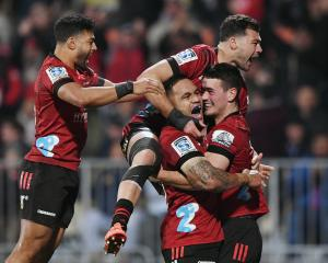Will Jordan (right) is mobbed by his Crusaders teammates after scoring against the Blues in...