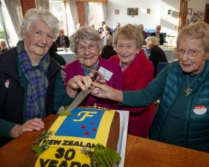 Marie Parry, 94, Pat Dean, 93, Fay Simon, 90, and Robyn Gosset, 89, cut into a special cake to...