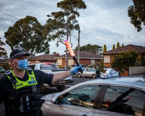 Victoria police interview drivers and passengers at a roadblock in Broadmeadows, Melbourne, as...