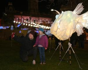 Naomi Daniels and daughter Elizabeth (4) pose for a selfie with a giant anglerfish lantern at the...
