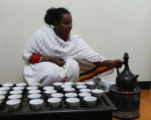 Sisaynesh Gebeyaw with the jebena (coffee pot) on a charcoal brazier and cups at the ready.