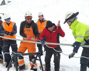 NZSki staff pull the cable taut as specialist metal rope splicer Hannes Koller thrashes the...