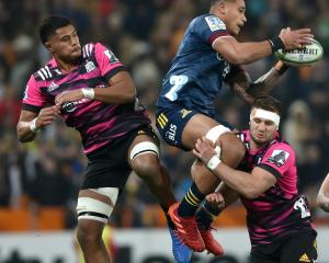 Highlanders flanker Shannon Frizell takes a high ball while under pressure from Chiefs players...