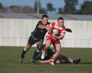 Clutha outside back Matt Barton looks to run away from the Clinton defence at the Balclutha...