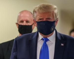 US President Donald Trump wears a mask while visiting Walter Reed National Military Medical...