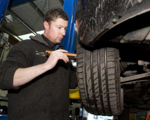 PD Auto Services director Nick Johnstone examines a client's car during a warrant of fitness...