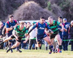 Woodlands back Tavasosi Taimavave goes past a couple of Marist defenders at Centrepoint Park on...