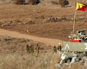 Israeli soldiers walk next to a tank in the Israeli-controlled Golan Heights near the Israel...