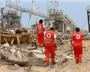 Lebanese Red Cross members walk amongst the rubble in Beirut. Photo: Reuters